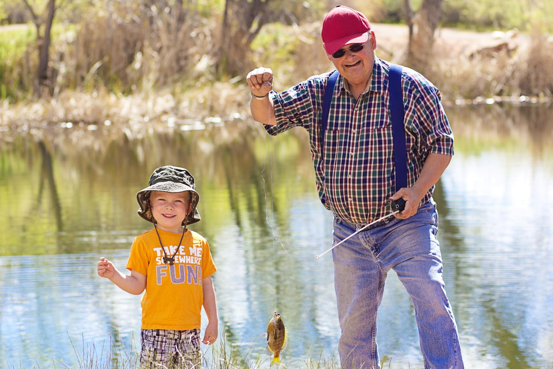 Little boy and his grandfather catching a fish