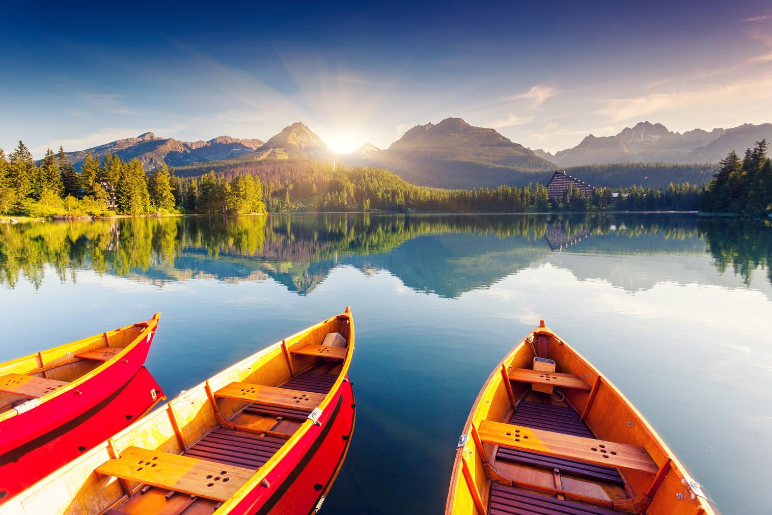 Boats at the edge of a lake with mountains in the background