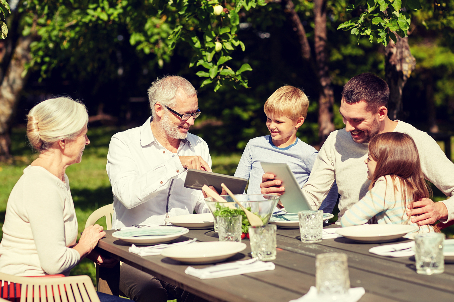 Multigenerational family sitting at a table looking at computers