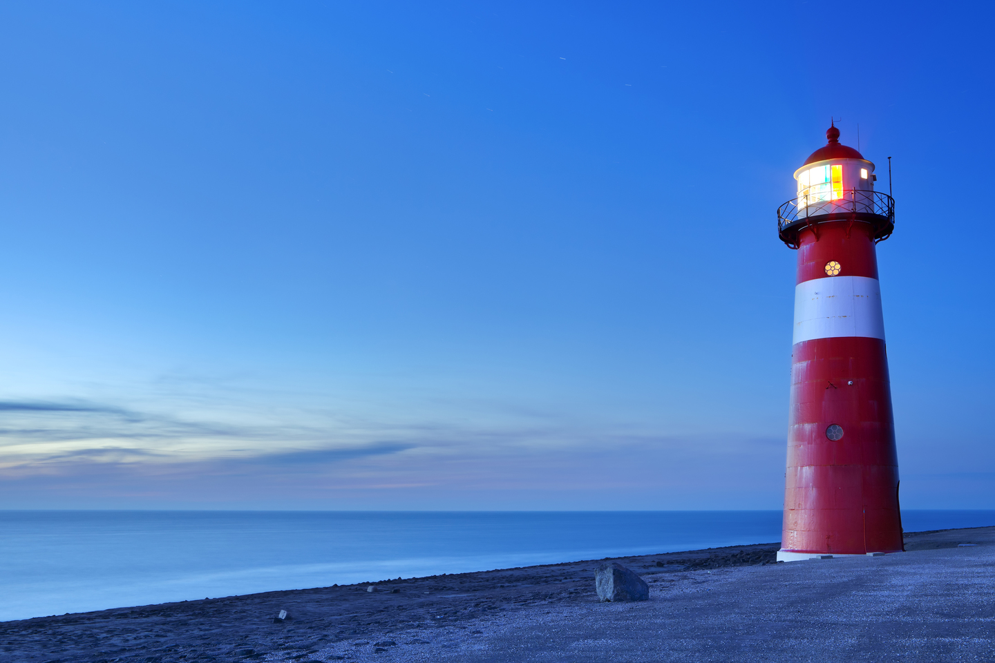 Red and white lighthouse on the sea at sunset
