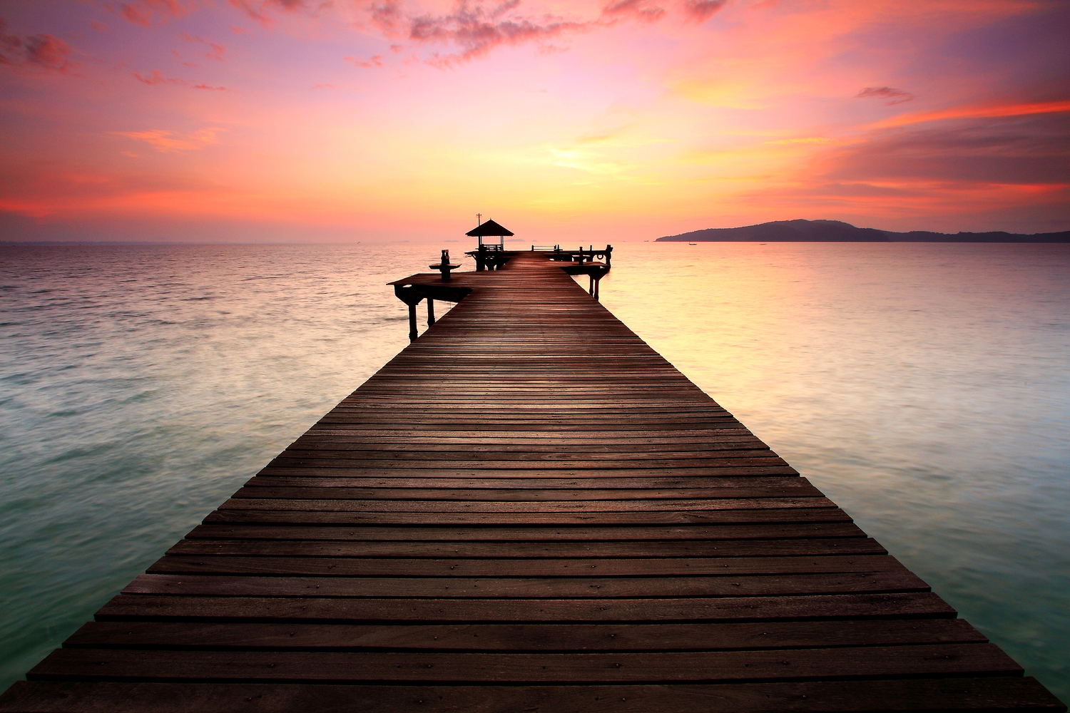 Dock leading out to the ocean at sunset