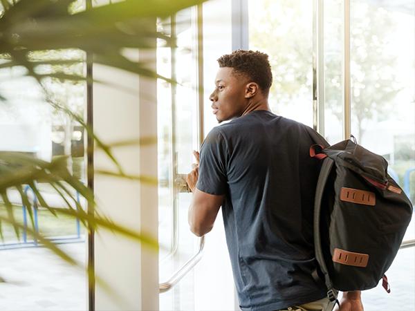 man with backpack walking through door